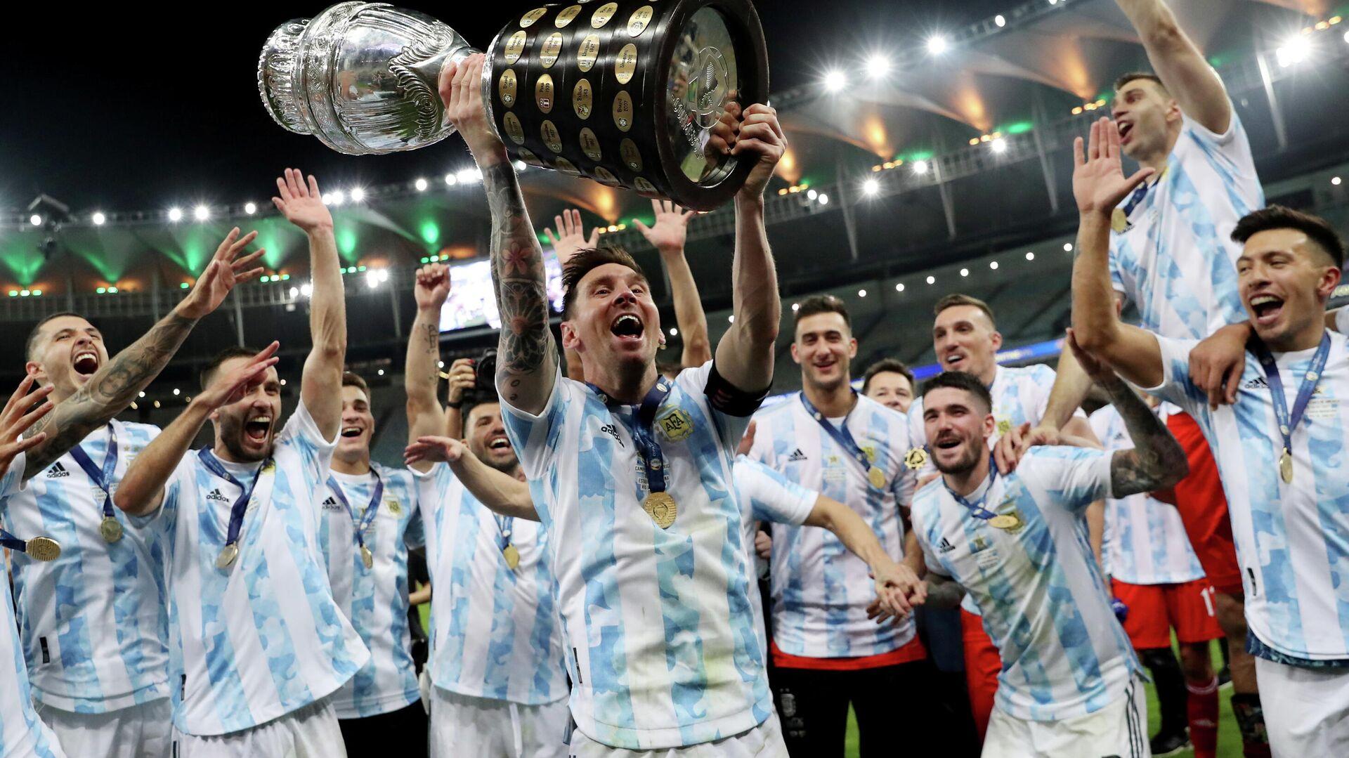 El futbolista argentino Lionel Messi y sus compañeros celebran con el trofeo en las manos su victoria sobre Brasil en la final de la Copa América 2021 celebrada en el Estadio de Maracaná, Río de Janeiro (Brasil), el 10 de julio de 2021  - Sputnik Mundo, 1920, 28.09.2021