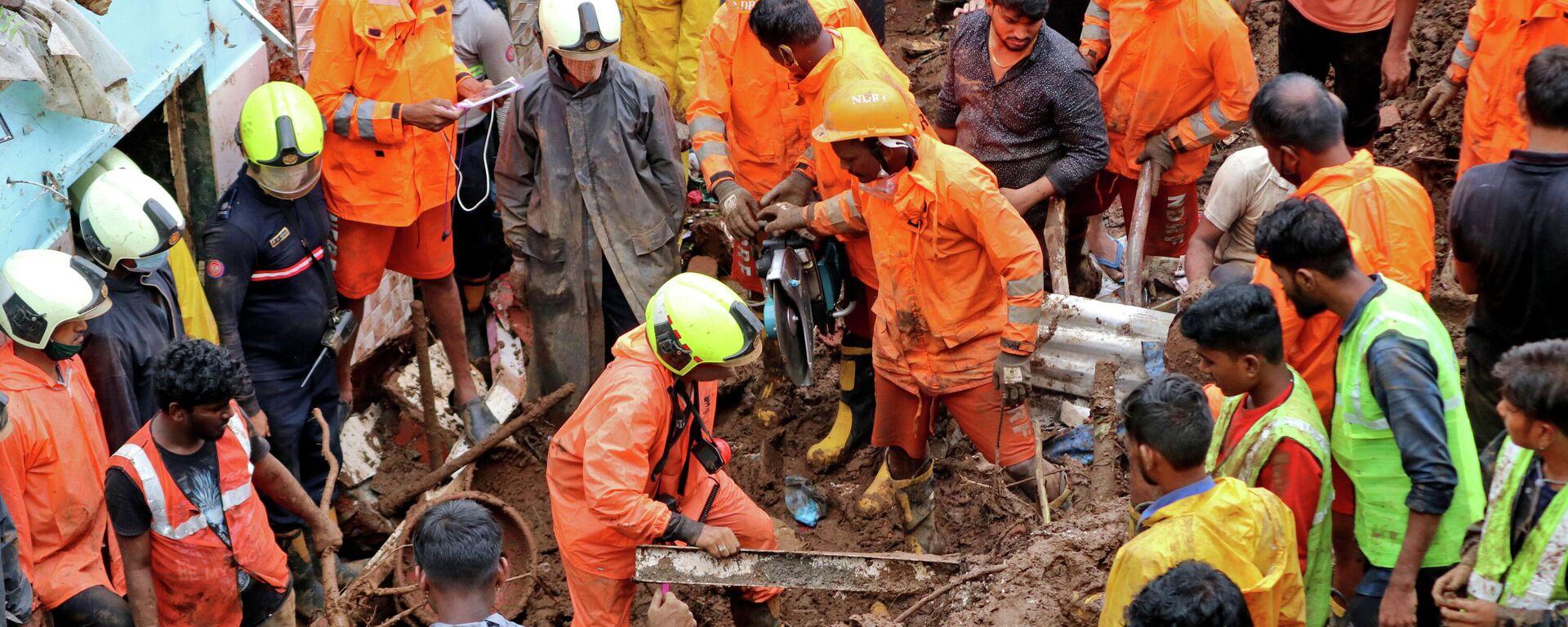 Los trabajadores de rescate retiran escombros mientras buscan sobrevivientes después de que una casa colapsara debido al deslizamiento de tierra causado por fuertes lluvias en Bombay, la India, el 18 de julio - Sputnik Mundo, 1920, 18.07.2021
