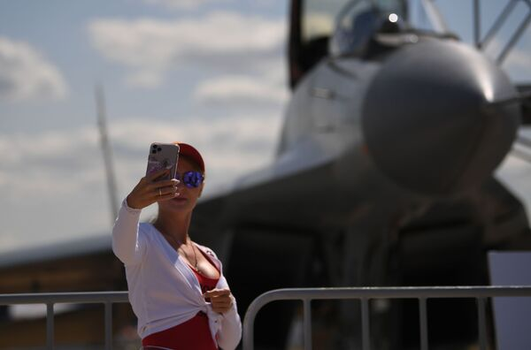 Una joven se toma una foto al lado de un MiG-35.  - Sputnik Mundo