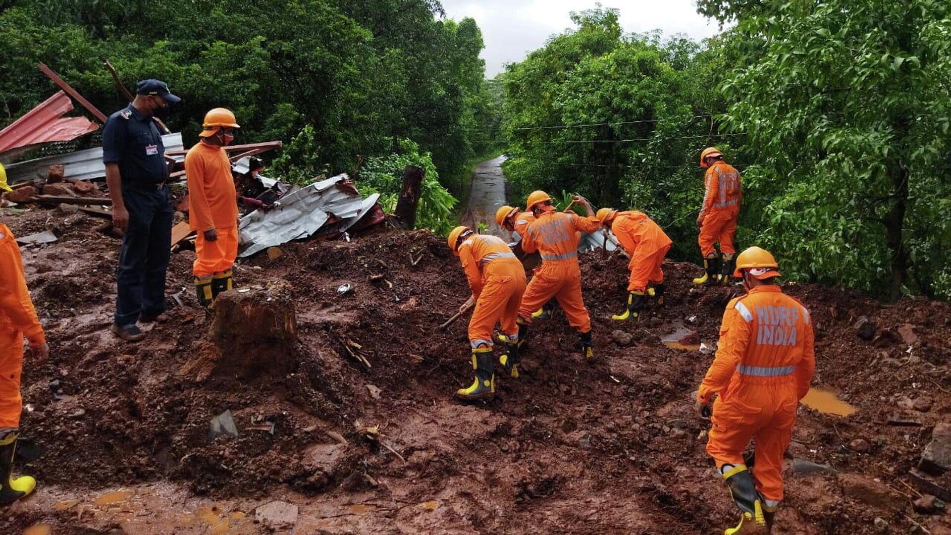 Miembros de la Fuerza Nacional de Respuesta a Desastres (NDRF) realizan una operación de búsqueda y rescate después de un deslizamiento de tierra provocado por fuertes lluvias en el distrito de Ratnagiri, estado de Maharashtra, India, el 25 de julio de 2021.  - Sputnik Mundo, 1920, 26.07.2021