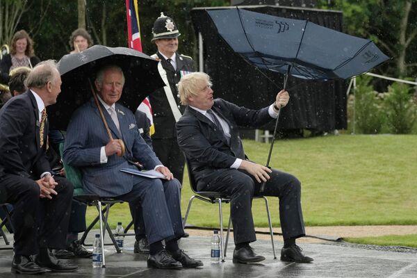 El príncipe Carlos y el primer ministro del Reino Unido, Boris Johnson, se refugian de la lluvia durante la inauguración de un monumento a la Policía del país. - Sputnik Mundo