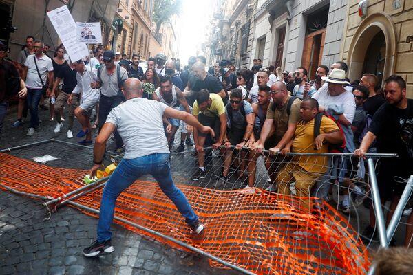 Unos manifestantes remueven una barrera instalada por la policía para bloquear su paso mientras marchan en contra del Green Pass, una especie de pasaporte COVID-19 que será obligatorio para cenas en interiores, eventos culturales y deportivos a partir de la próxima semana, en Roma (Italia). - Sputnik Mundo
