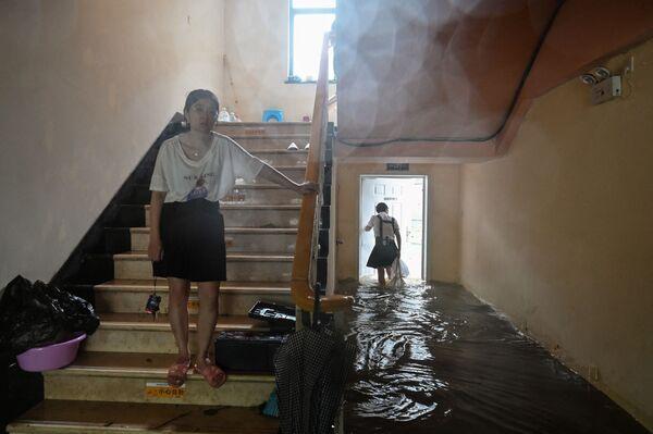 Unas personas caminan en un hotel inundado en Ningbo (China) mientras el tifón In-Fa azota la costa este del país. - Sputnik Mundo