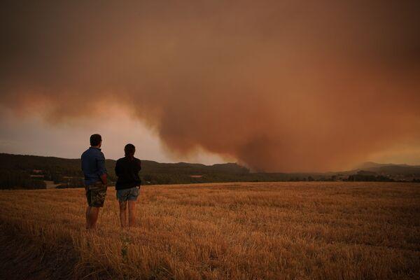Unos lugareños observan un incendio forestal cerca de Tarragona, en Cataluña (España). - Sputnik Mundo