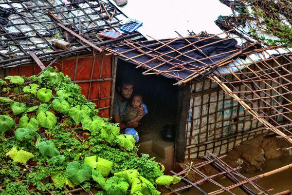 Un refugiado rohinyá y su hijo miran hacia afuera desde el interior de su refugio inundado tras las fuertes lluvias que azotaron el campo de refugiados de Kutupalong (Bangladés). - Sputnik Mundo