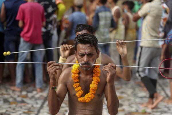 Unos devotos, con las mejillas perforadas como parte de un ritual, se preparan para comenzar una peregrinación anual al templo de la diosa hindú Shitalá en Jammu (la India). - Sputnik Mundo