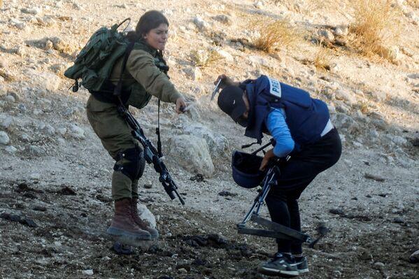 Una soldado israelí rocía gas pimienta a un periodista durante una protesta contra los asentamientos israelíes en Cisjordania. - Sputnik Mundo