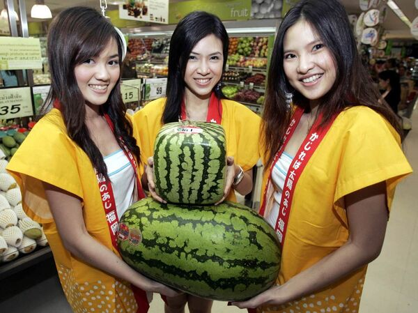 Unas modelos posan con unas sandías insólitas importadas de Japón, durante el Festival de Frutas Japonesas celebrado en Bangkok. - Sputnik Mundo