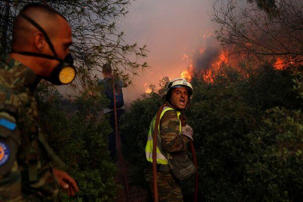 Unos bomberos voluntarios intentan controlar el fuego a las afueras de Atenas. - Sputnik Mundo