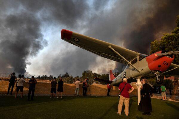 Los vecinos se congregan en la entrada del aeropuerto militar en Tatoi, al norte de la capital griega. - Sputnik Mundo