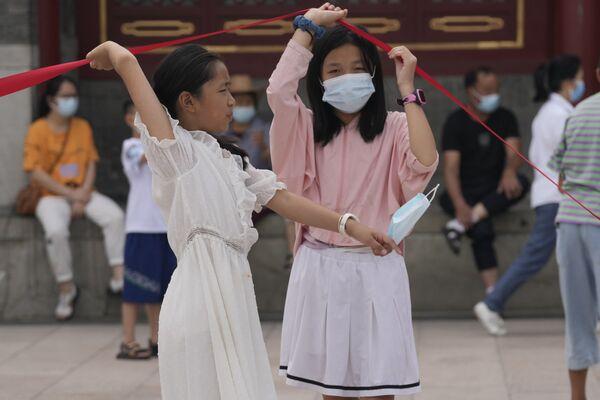 La variante delta del coronavirus está desafiando la costosa estrategia china de imponer un aislamiento casi total en cualquier foco. En la foto: dos niñas con mascarillas levantan una barrera en Pekín. - Sputnik Mundo