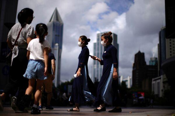 Al 1 de agosto, en los centros médicos de Wuhan había 18 pacientes con diagnóstico confirmado de COVID-19. En la foto: varias personas caminan por las calles con mascarillas en Shanghái, China. - Sputnik Mundo