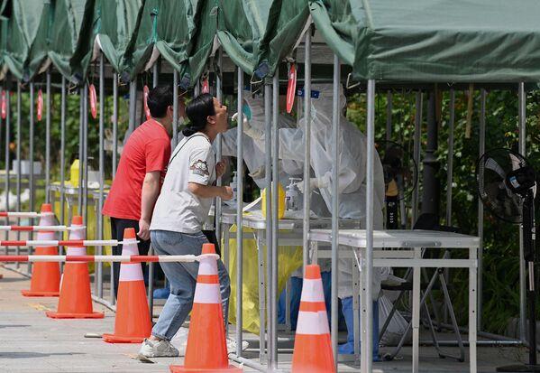 Las autoridades de China decretaron confinamientos parciales en varias ciudades afectadas. En la foto: un trabajador sanitario realiza un hisopado a una mujer en una estación de recogida de muestras de ácido nucleico en un parque de Pekín. - Sputnik Mundo