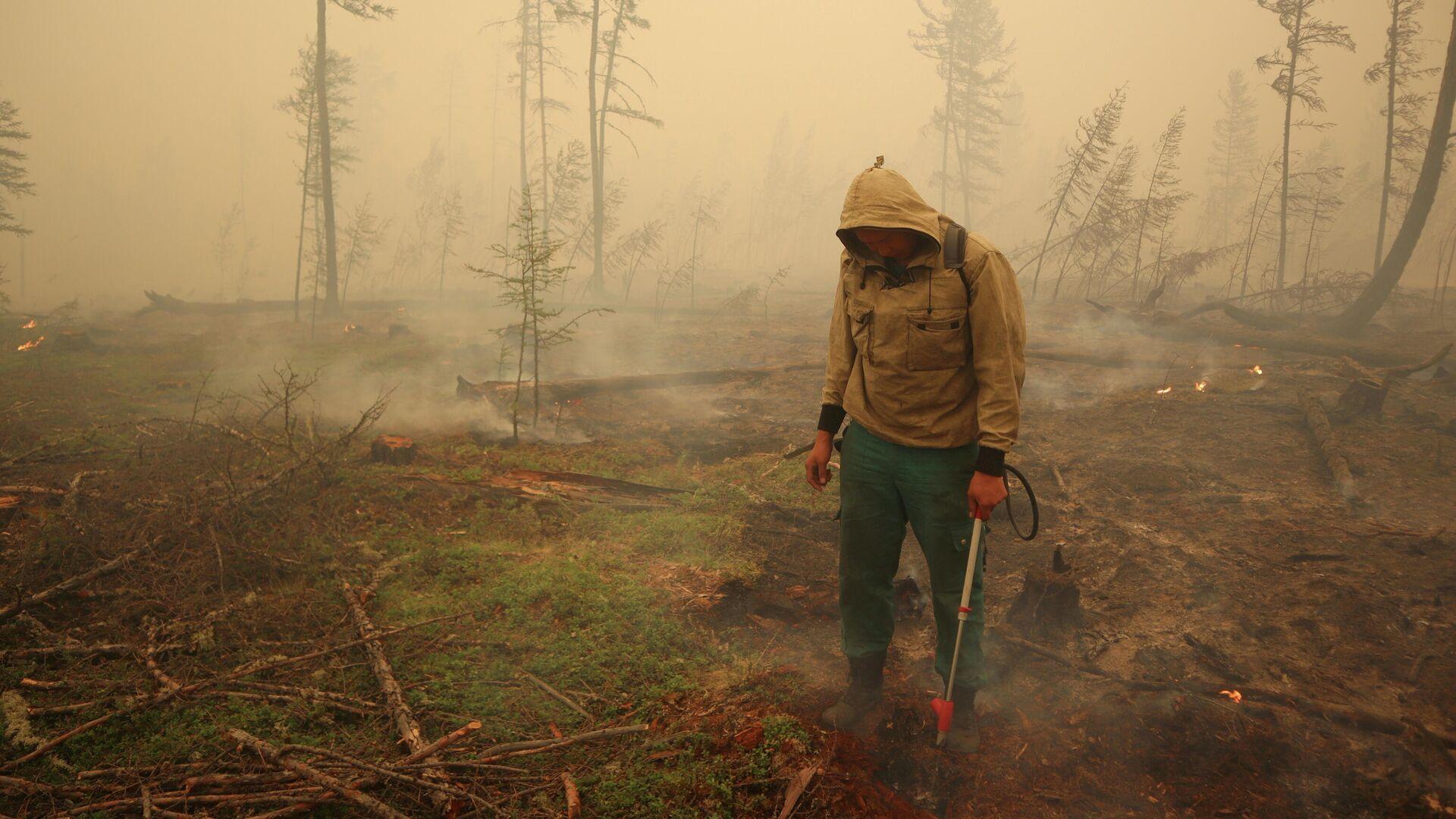 Un especialista del servicio local de protección forestal extingue un incendio forestal cerca del pueblo de Magaras en la región de Yakutia, Rusia, el 17 de julio de 2021 - Sputnik Mundo, 1920, 19.08.2021