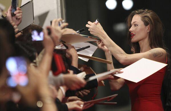Angelina Jolie nació zurda, lo que no le impide criar a seis hijos, actuar en películas taquilleras y hacer obras de caridad. Durante el rodaje de la cintaLara Croft, la actriz incluso utilizó una pistola especial para zurdos.En la foto: Angelina Jolie firma autógrafos antes del estreno de Moneyballen Tokio (Japón), 2011. - Sputnik Mundo