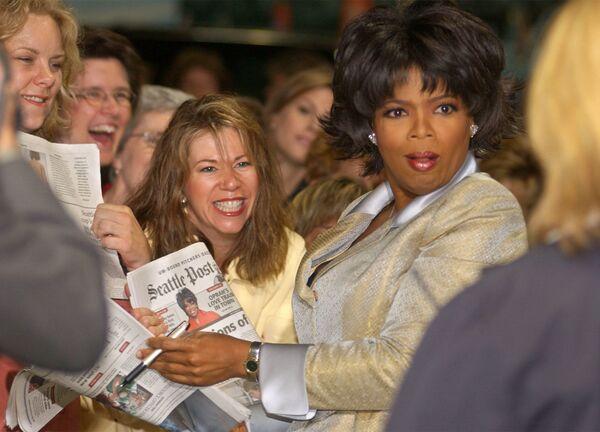 La famosa presentadora de televisión Oprah Winfrey también es zurda.En la foto: Oprah Winfrey con unos fans en Seattle (EEUU), 2003. - Sputnik Mundo