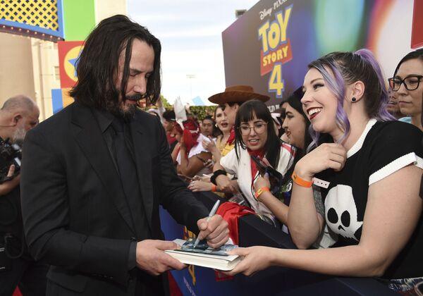 Si bien es zurdo, el actor Keanu Reeves, al igual que Lady Gaga, sabe tocar la guitarra a la diestra.En la foto: Keanu Reeves firma autógrafos antes del estreno mundial de Toy Story 4 en Los Ángeles (EEUU), 2019. - Sputnik Mundo