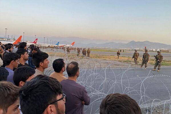 El Departamento de Defensa de EEUU ha ordenado el envío de 1.000 soldados adicionales a Kabul para ayudar a evacuar a los ciudadanos estadounidenses. En la foto: los residentes afganos observan a varios soldados estadounidenses detrás de un alambrado de seguridad que les impide la entrada. - Sputnik Mundo