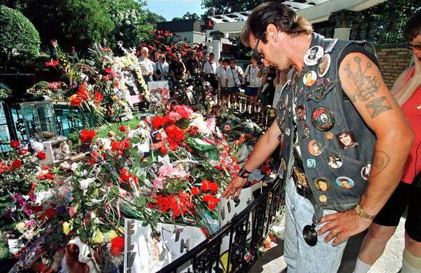 Sin embargo, todo indicaba que Presley no tenía ganas de morir. El cantante estaba a punto de iniciar una gira, su nuevo álbum acababa de salir a la venta y, además, se preparaba para casarse con la actriz Ginger Aldean.En la foto: un fanático de Elvis visita su tumba en el día del 20 aniversario de su muerte, en 1997. - Sputnik Mundo