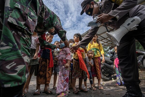 Esta impresionante imagen que muestra a los miembros de la Guardia Nacional y la Policía de la isla de Bali repartiendo mascarillas entre los niños, captada por Edy Gautama, ocupó el tercer lugar en la categoría Los héroes de la pandemia. El fotógrafo la tituló Guardian Angel (Un ángel de la guarda). - Sputnik Mundo