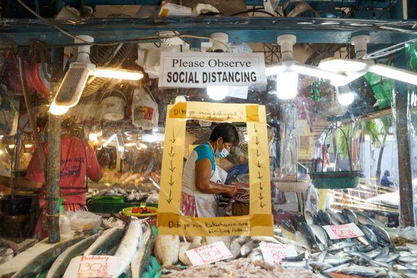 Aquarium, del filipino JL Javier, ocupó el primer lugar en la categoría La nueva normalidad. Muestra a una vendedora de pescado en el mercado de Manila. - Sputnik Mundo