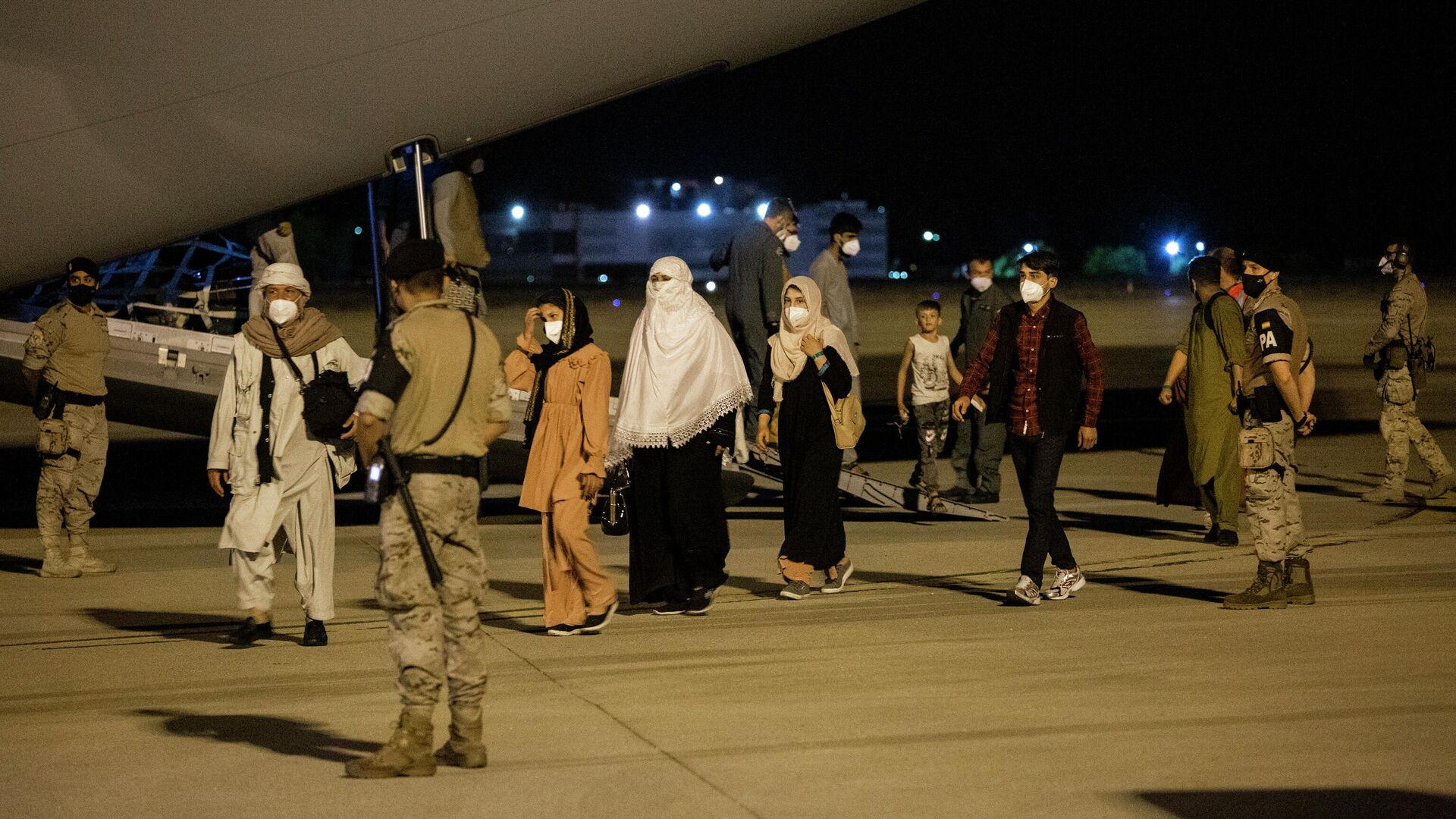 Varias personas repatriadas llegan a la pista tras bajarse del avión A400M en el que ha sido evacuados de Kabul, a 19 de agosto de 2021, en Torrejón de Ardoz, Madrid - Sputnik Mundo, 1920, 28.09.2021