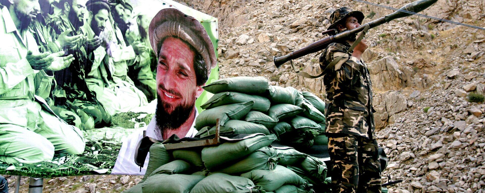 Soldado afgano frente el poster con Ahmad Shah Masud, señor de la guerra de Afganistán conocido como 'el león de Panshir' (archivo) - Sputnik Mundo, 1920, 20.08.2021