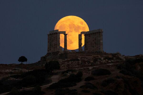 La luna de este agosto, en particular, es especial pues se trata de una luna azul. El nombre, sin embargo, no indica el color que tendrá el satélite natural en el cielo.En la foto: la luna de esturión se eleva sobre el templo de Poseidón en el cabo de Sunio, cerca de Atenas (Grecia). - Sputnik Mundo