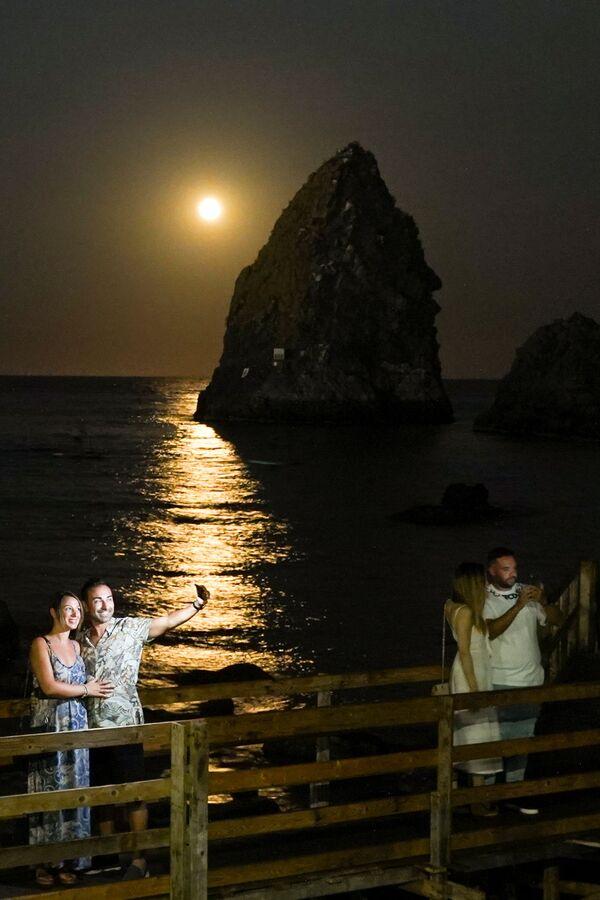 Llamada luna azul 'estacional', aparece solo una vez cada tres años aproximadamente.En la foto: la luna de esturión se ve en el cielo de I Faraglioni di Acitrezza en Catania (Italia). - Sputnik Mundo