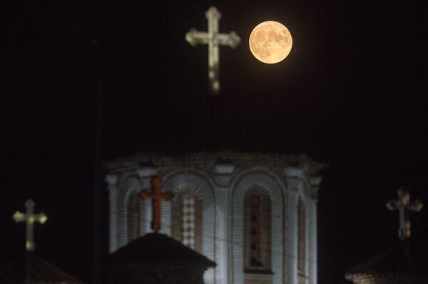 A menudo se usa el término 'luna azul' indistintamente para nombrar también a una ocurrencia similar, cuando hay dos plenilunios en un mismo mes.En la foto: la luna de esturión se eleva detrás de la iglesia de San Juan Bautista en Skopie (Macedonia del Norte). - Sputnik Mundo