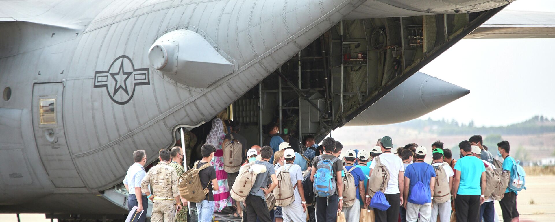 Un grupo de jóvenes y familias afganas, se dirigen a subir a un avión estadounidense para ser trasladados a Alemania, en la base aérea de Torrejón de Ardoz, a 24 de agosto de 2021, en Madrid (España).  - Sputnik Mundo, 1920, 25.08.2021