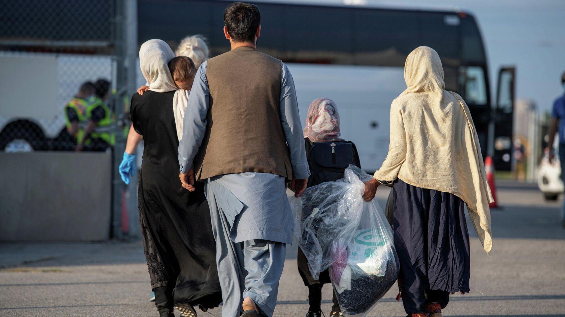 Los refugiados afganos que apoyaron la misión de Canadá en Afganistán se preparan para abordar los autobuses después de llegar a Canadá, en el Aeropuerto Internacional Toronto Pearson el 24 de agosto de 2021 - Sputnik Mundo, 1920, 23.09.2021