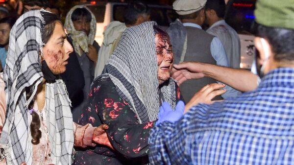 Mujeres lloran a los heridos y fallecidos en el ataque terrorista en Kabul. - Sputnik Mundo