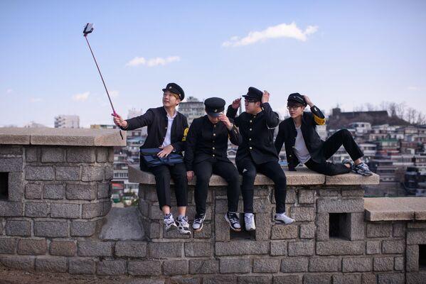 Corea del Sur tiene una política de uniformes escolares muy estricta que, sin embargo, puede variar de un colegio a otro.En la foto: escolares coreanos con uniformes de los años 70 en una excursión a la aldea del arte en el parque Naksan de Seúl, 2016. - Sputnik Mundo