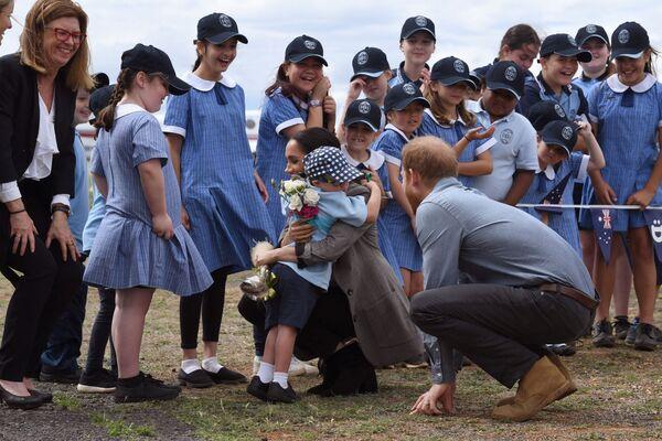 El uniforme escolar en Australia es similar al uniforme escolar británico tradicional, pero es más abierto y ligero, y con un tocado.En la foto: escolares australianos con el príncipe Harry y su esposa Meghan en el aeropuerto de Dubbo, 2018. - Sputnik Mundo