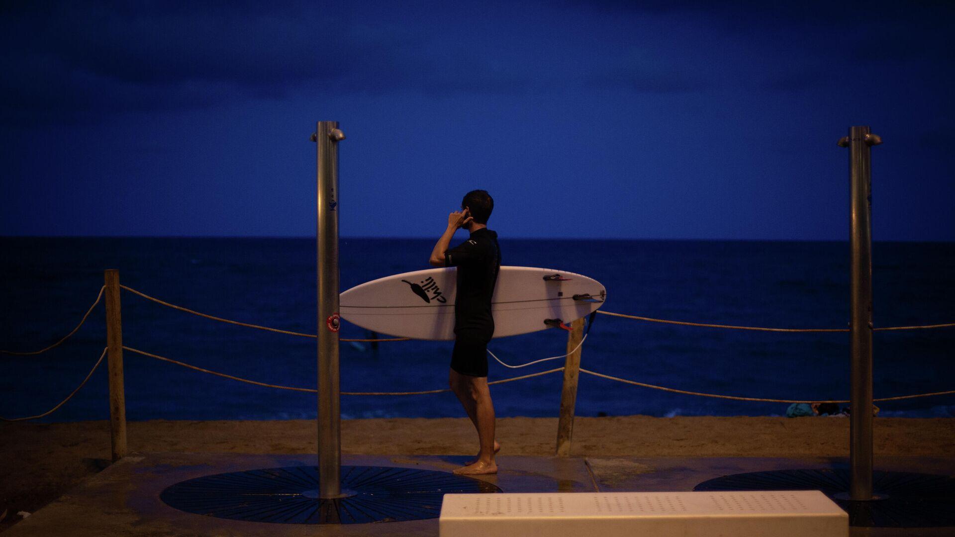 Imagen referencial de un joven que practica surf en una playa. - Sputnik Mundo, 1920, 03.09.2021