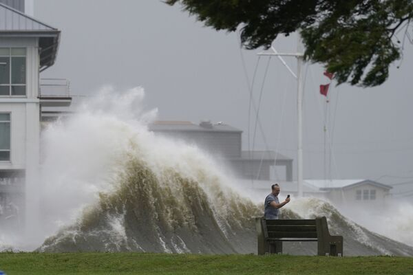 Un hombre toma fotos de las altas olas a lo largo de la orilla del lago Pontchartrain, mientras se acerca el huracán Ida, el 29 de agosto de 2021, en la ciudad de Nueva Orleans, EEUU. - Sputnik Mundo