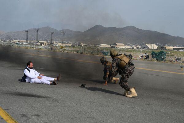 Los combatientes de las fuerzas especiales talibanes Badri (a la derecha) y un periodista se levantan después de caerse de un auto en el aeropuerto de Kabul, el 31 de agosto de 2021. Mientras tanto, EEUU retiró a sus tropas de Afganistán al poner fin a una brutal guerra de 20 años. - Sputnik Mundo