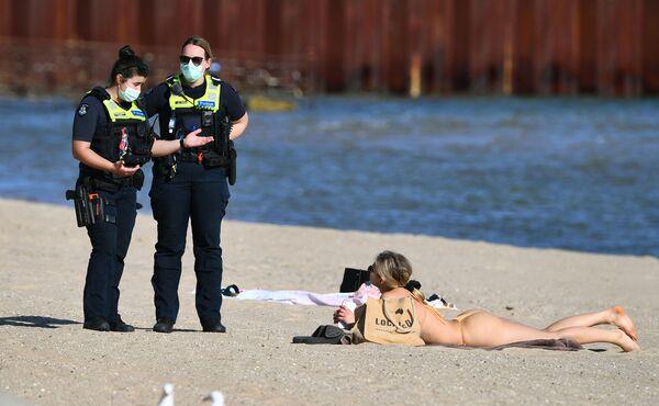 Agentes de Policía hablan con una mujer que disfruta del clima primaveral inusualmente cálido en la playa de St. Kilda en Melbourne, el 2 de septiembre de 2021, mientras la ciudad permanece cerrada debido a la propagación de la variante delta del coronavirus. - Sputnik Mundo