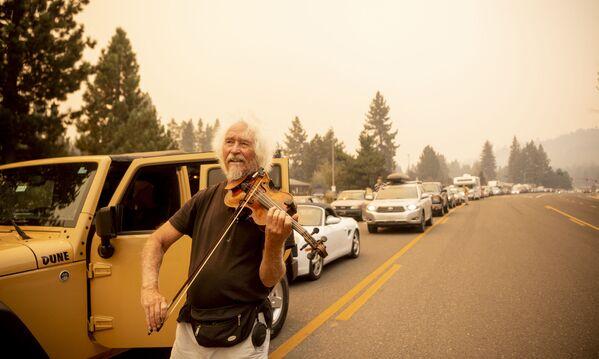 Mel Smothers toca el violín mientras permanece atrapado en el tráfico con los evacuados a medida que los vecinos intentan huir del incendio Caldor en el lago Tahoe, California, el 30 de agosto de 2021. Se han quemado al menos 650 estructuras y miles más están amenazadas a medida que el fuego avanza hacia la zona turística. - Sputnik Mundo