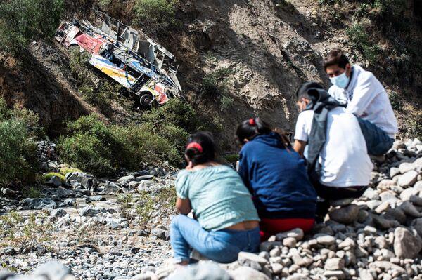 Varias personas sentadas cerca del lugar donde un autobús se precipitó por un acantilado en Matucana, al este de Lima, el 31 de agosto de 2021. Al menos 32 personas murieron, incluidos dos niños, y otras veinte resultaron heridas. - Sputnik Mundo