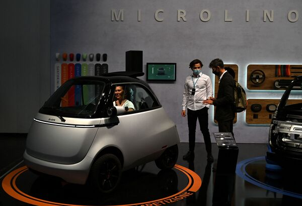 Una mujer ingresa a la cabina del coche burbuja eléctrico Microlino 2.0. - Sputnik Mundo