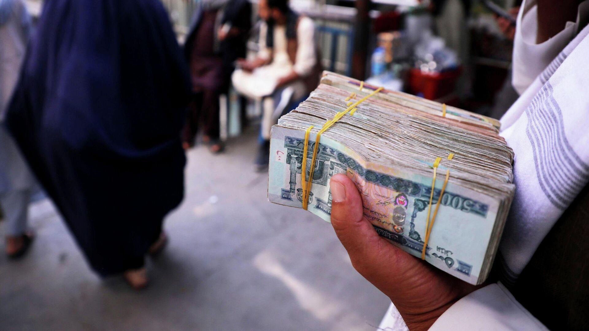 Un hombre con billetes de afganis en Kabul - Sputnik Mundo, 1920, 09.09.2021