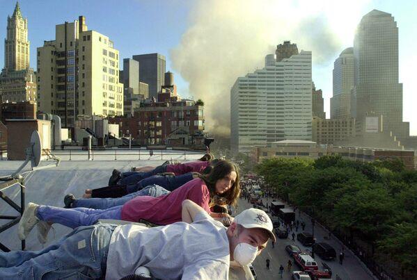 El vuelo 175 de United Airlines chocó contra la torre sur del WTC a las 9:03 (hora local) entre los pisos 78 y 85. En la foto: la gente observa la operación de rescate después del ataque terrorista del 11 de septiembre desde el techo de una casa en Greenwich St. - Sputnik Mundo