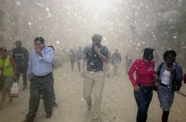 1.366 personas murieron en el WTC-1, algunas de ellas en el momento de la colisión, el resto debido a un incendio y al derrumbe del edificio. En la foto: personas huyen del World Trade Center tras los ataques a las torres gemelas. - Sputnik Mundo