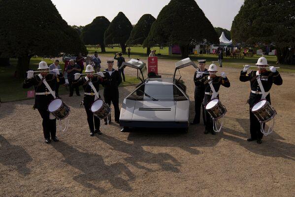 A pesar de su imponente motor, la falta de tecnologías modernas se hace evidente al observar la aceleración del Bulldog: para llegar de 0 a 100 km/h le hacen falta 5,1 segundos. A modo de comparación, el Tesla Model S Plaid necesita poco más de 2 segundos.En la foto: los tamborileros de la Orquesta Real de la Armada del Reino Unido posan para las fotos después de la presentación del Aston Martin Bulldog restaurado.   - Sputnik Mundo