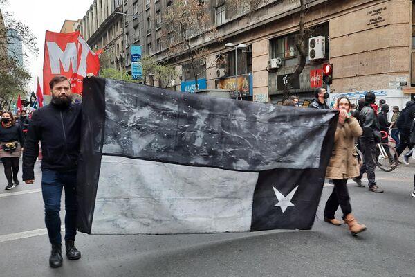 Una bandera chilena de luto y al revés durante la marcha para conmemorar a las víctimas de la dictadura chilena - Sputnik Mundo
