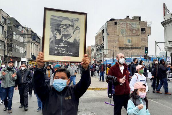 Un manifestante lleva un cuadro con la foto de Salvador Allende - Sputnik Mundo