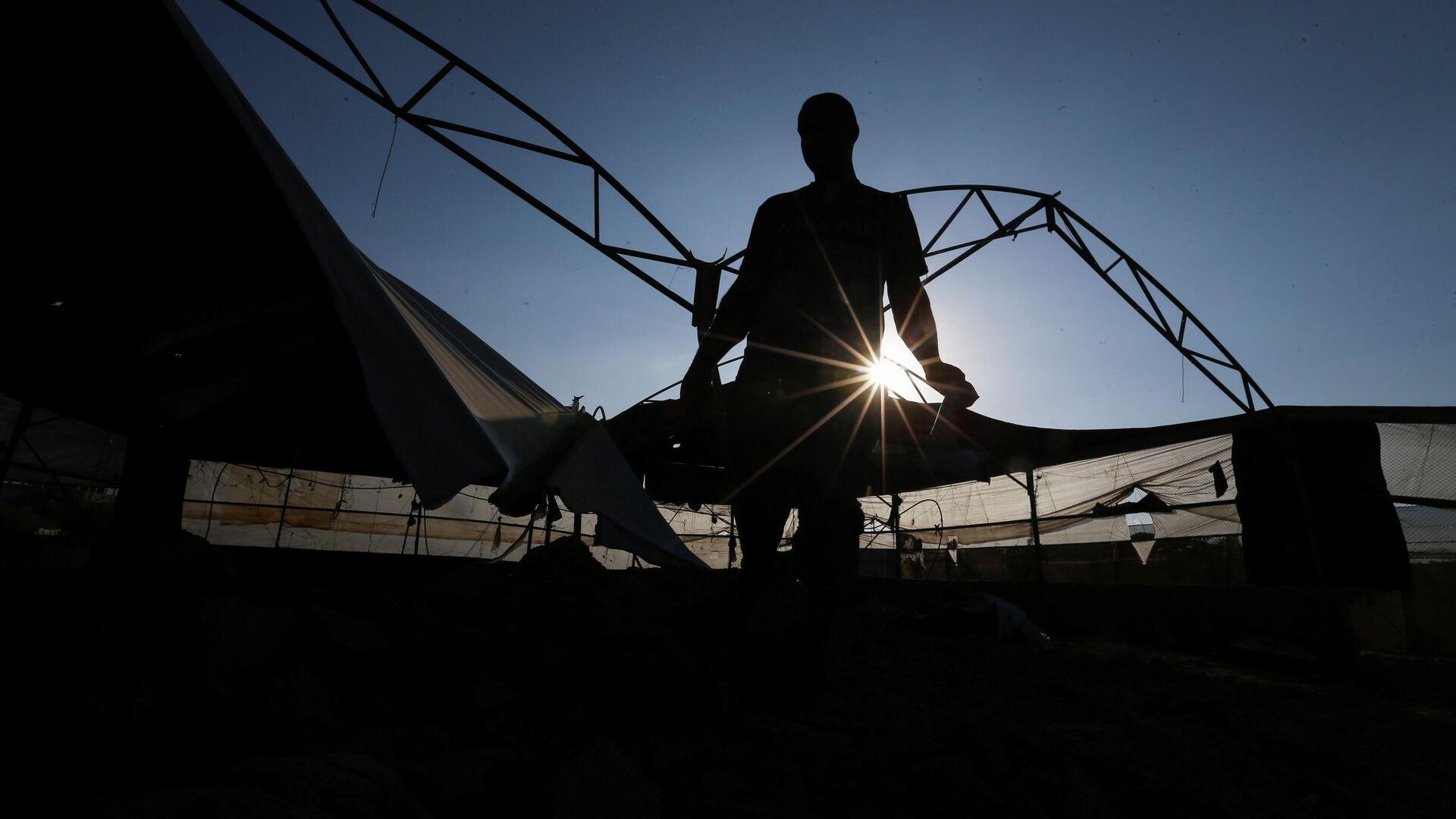 Un palestino inspecciona el lugar de un ataque aéreo israelí tras el lanzamiento de cohetes palestinos contra Israel, en el sur de la Franja de Gaza, el 12 de septiembre de 2021 - Sputnik Mundo, 1920, 12.09.2021