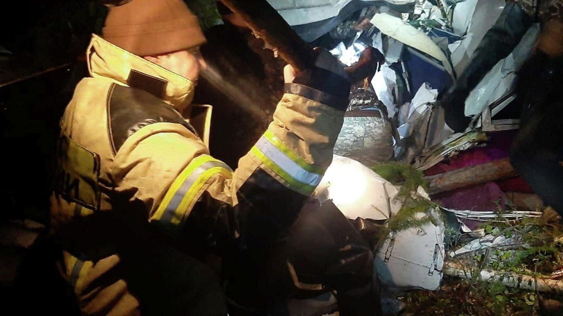 Especialistas en emergencias trabajan en el lugar del accidente de la aeronave L-410 cerca de la localidad de Kazáchinskoe, provincia de Irkutsk, Rusia, 13 de septiembre de 2021.  - Sputnik Mundo, 1920, 13.09.2021